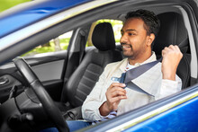 Transport, Safety And People Concept - Happy Smiling Indian Man Or Driver Fastening Seat Belt In Car