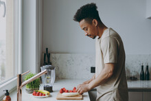 Side View Young Serious Single African American Man 20s Wearing Casual Clothes Prepare Sweet Salad Chop Cut Fruit Cooking Food In Light Indoor Kitchen At Home Alone. Healthy Diet Lifestyle Concept