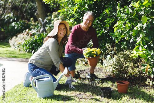 Portrait of happy senior caucasian couple gardening, looking to camera in sunny garden