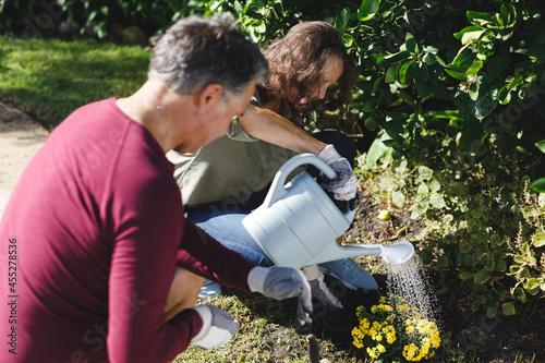 Happy senior caucasian couple gardening together in sunny garden