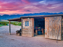 Old Wooden Shack On The Backdrop Of A Beautiful Sunset And Hills