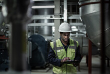 African American Male Engineer Inspecting An Industrial Plant Room
