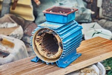 Burnt Out Electric Engine With Light Blue Metal Case Stands On Long Wooden Board On Waste Products Background Close View
