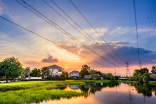 Line Of High Voltage Power With Electricity Transmission Close To Residential Buildings. Power Transmission Tower In City With Urban Area.
