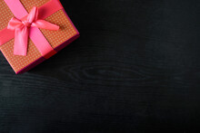 Red Gift Box With Pink Bow On The Background Of Black Wood. Place For Text