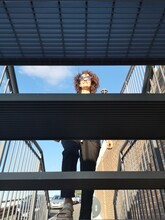 View From Below Of Woman Climbing Iron Stairs