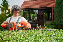 Professional Gardener Wearing Uniform, Protective Gloves And Face Defender Using Electric Hedge Trimmer For Shaping Bushes. Seasonal And Manual Work Concept.
