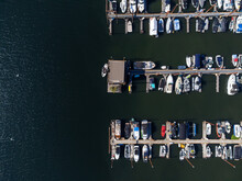 Sea Harbor, Port, Pier. There Are Many Moored Yachts, Boats, Sailboats. Sparks Of Stars Are Reflected In The Deep Blue Sea Water. Minimalism. View From Above. Shooting From A Drone.