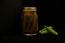 Okra, Jar Of Pickled Okra In Brine With Fresh Okra On A Black Background, End Of Summer