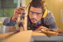 Portrait Of A Carpenter Using A Circular Saw In A Workshop, Thailand