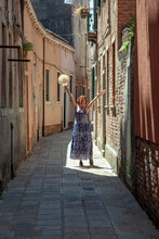 Cheerful, Cheerful Woman In A Sundress In The Rays Of Sunlight On A Narrow Street Of Venice