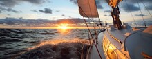 Yacht Sailing In An Open Sea At Sunset. Close-up View Of The Deck, Mast And Sails. Clear Sky After The Rain, Dramatic Glowing Clouds, Golden Sunlight, Waves And Water Splashes, Cyclone. Epic Seascape