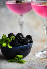 Two Blackberry And Lemon Cocktails In Cocktail Glasses And A Bowl Of Blackberries