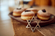 Close-up Of Star Of David With Traditional Jewish Jam Filled Donuts On Hanukkah.