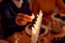 Close-up Of Man Lights Candles In Menorah During Hanukkah Meal At Home.