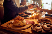 Close-up Of Traditional Hanukkah Food With Family Toasting In Background.