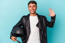 Young Biker Man Holding Helmet Isolated On Blue Background  Smiling Cheerful Showing Number Five With Fingers.