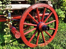 Old Carriage Or Cart. Summer Day. Traditional Rural Horse-drawn Carriage. The Chariot Is Red With Flowers. Horse Cart. Retro Wooden Wheel. Garden And Lawn Decoration