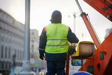 Worker Operate Aerial Platform. Elevating Work, Worker Operated Hydraulic Platform . Crane Operator In Uniform Controls Telescope Bucket. Utility Worker Repairing Street Light, Controls Cherry Picker