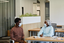 Medical Nurse In Protective Suit And Medical Mask Talking To Patient Before He Can Get Vaccine Against COVID-19