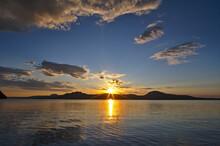 夜明けの空に朝陽の輝く北海道の屈斜路湖。