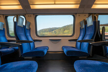 Blue Empty Opposing Seats In A Moving Train. Large Window With Blurred Landscape, Daytime, Summer, No People.