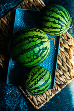 Overhead View Of Three Watermelons On A Plate On A Place Mat