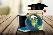 Graduated Hat And World Globe On The Desk
