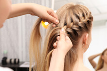 Professional Stylist Braiding Client's Hair In Salon