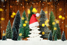 Many Christmas Trees With Golden Lights And Santas Red Hat On A White Tree. Merry Christmas And A Happy New Year Banner. Seasons Greetings Card