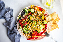 Chickpea, Red Pepper, Cauliflower, Cucumber And Tomato Salad Bowl With Flatbread And A Glass Of Lemon Water