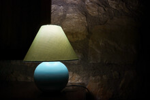 Bedside Night Illuminated Lampshade Light Lamp With Round Blue Base Near Stone Wall In Dark Room. Interior Design Elements Background