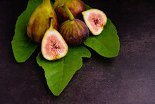 Figs Fruit Are On Fresh Green Leaves On Vintage Background. High Vitamins Fruit. Close-up Photo. Concept Of Healthy Fruits And Healthcare