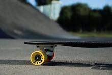 Modern Black Skateboard With Colorful Wheels On Asphalt Road Outdoors, Closeup
