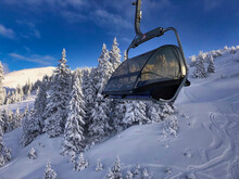 Scenic View Of Snowy Forest With Tall Trees And Chairlift On Sunny Day