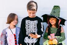 Children In Halloween Costumes Using Smartphone