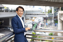 Asian Business Man Investor Stock Trading In Laptop Computer On Street. Handsome Businessman Working Outdoors With Computer