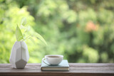 White coffee cup and notebook with devil ivy plant on wooden table