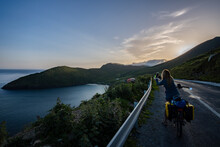 Female Traveler Cyclist Taking A Photo Of Sheep And A Panoramic View Of Keem Bay In Achill Island Ireland