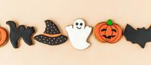 Various Halloween Gingerbread Cookies - Jack O'Lanterns, Ghosts, Bat And Black Hat On Beige Background. Banner