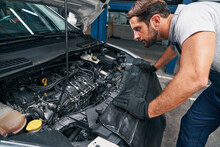 Young Attentive Repairman Is Examining Car Engine