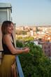 Mujer mirando asomada a su terraza con edificios de fondo. Madrid desde el cielo. Mujer observando la calle. Chica pensando. Chica sonriendo
