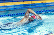 Leinwandbild Motiv Professional male swimmer in swimming cap and goggles in motion and action during training at pool, indoors. Healthy lifestyle, power, energy, sports movement concept