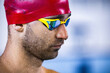 Leinwandbild Motiv Close-up portrait of young man, swimmer in red swimming cap and goggles preparing to training at pool, indoors. Healthy lifestyle, power, energy, sports movement concept
