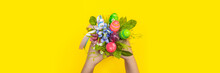 Gift Bouquet For Easter. Handmade Bouquet With Decorative Easter Eggs And Flowers In The Hands Of A Child. Child Holding A Bouquet In His Hands On A Yellow Background