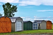Various Styles Of Wooden Sheds On Display. American Shed Is Typically A Simple, Single-story Roofed Structure In A Back Garden Or On An Allotment That Is Used For Storage, Hobbies, Or As A Workshop.