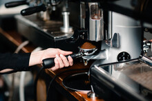 Barista Holding Portafilter Filling It With Ground Coffee For Espresso Shot