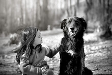 Grayscale Photo Of Girl Sitting Beside Dog Outdoor