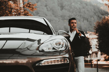 Man In Black Suit Holding Cigar Standing Beside Black Mercedes Benz Coupe