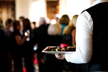 Man In Dress Shirt Holding Tray With Food